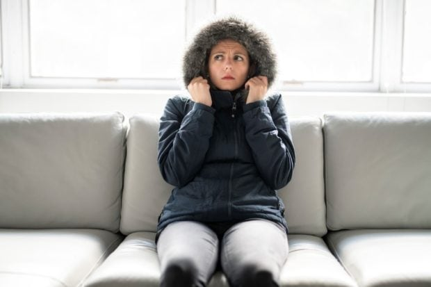 Woman in a parka on her couch, cold because of a broken heating system.