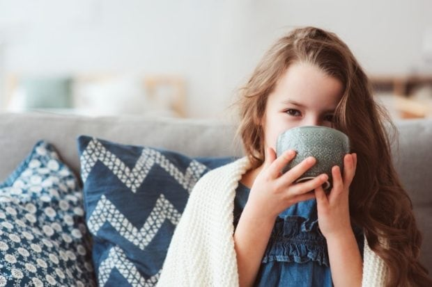 Little girl with a blanket around her sipping hot tea to keep warm because her furnace broke.