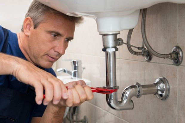 man adjusting sink pipe