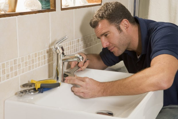 An Albuquerque plumber repairing a faucet and clogged drain.
